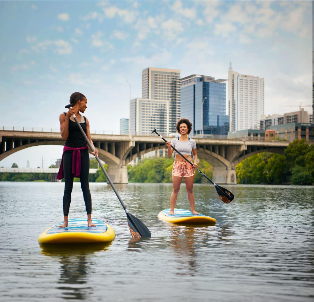 Two Women Stand up paddleboarding on Lady Bird Lake In Austin, TX