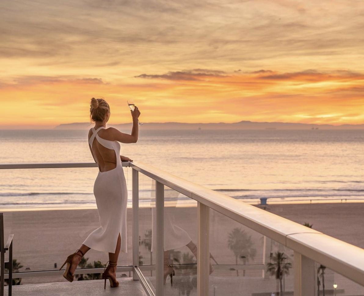 Woman on a balcony at a Huntington Beach hotel raises her glass in a toast