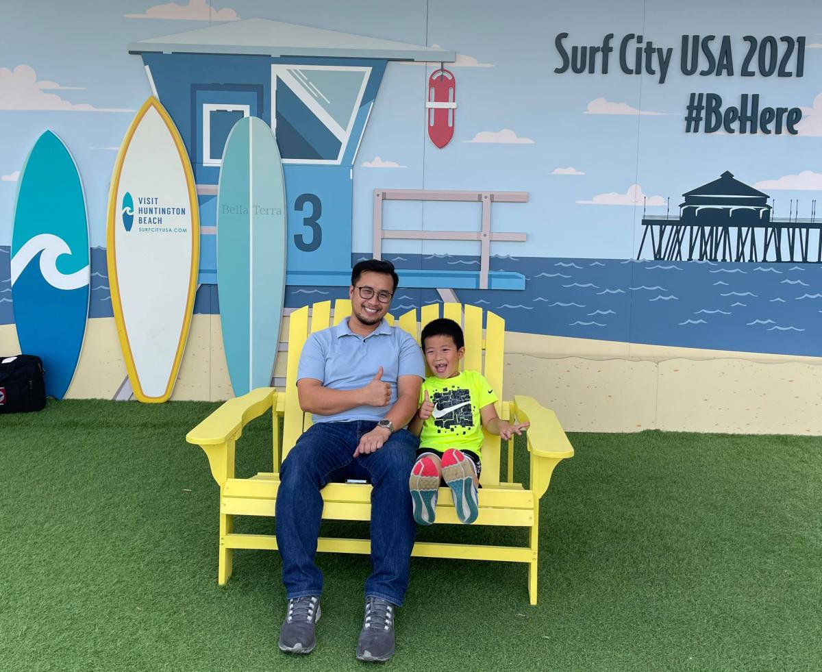 Father and son sitting on a yellow bench at Bella Terra.