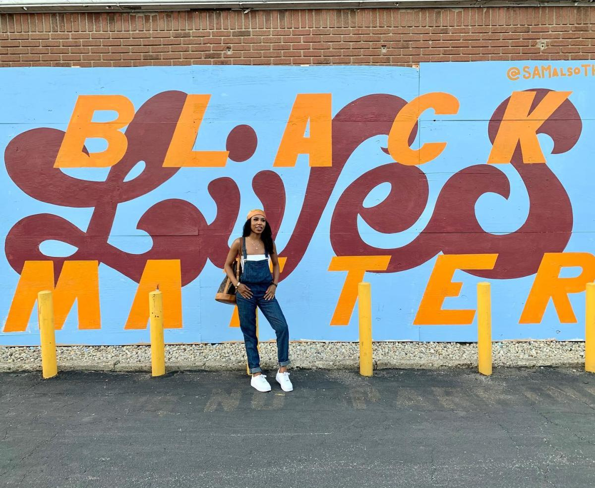 Girl poses in front of Black Lives Matter mural