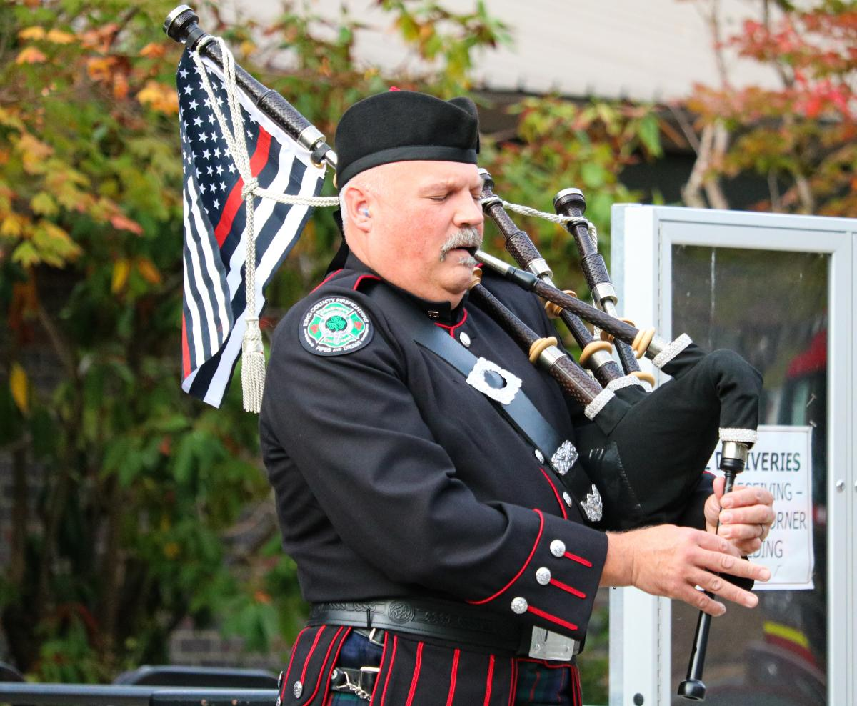 Firefighter and piper playing at City Hall