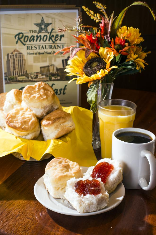 Biscuits with jam, coffee, orange juice, a menu, and flowers sit on a table at The Roanoker.