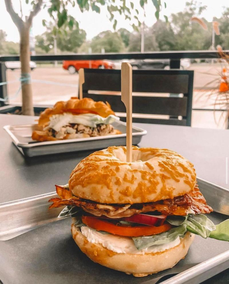 bagel breakfast sandwich on a platter on a table in the outdoor patio dining area at Crescendo coffee and more