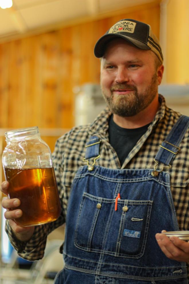 Chris Prillaman - Twin Creeks Distillery - Holding a bottle of liquor.