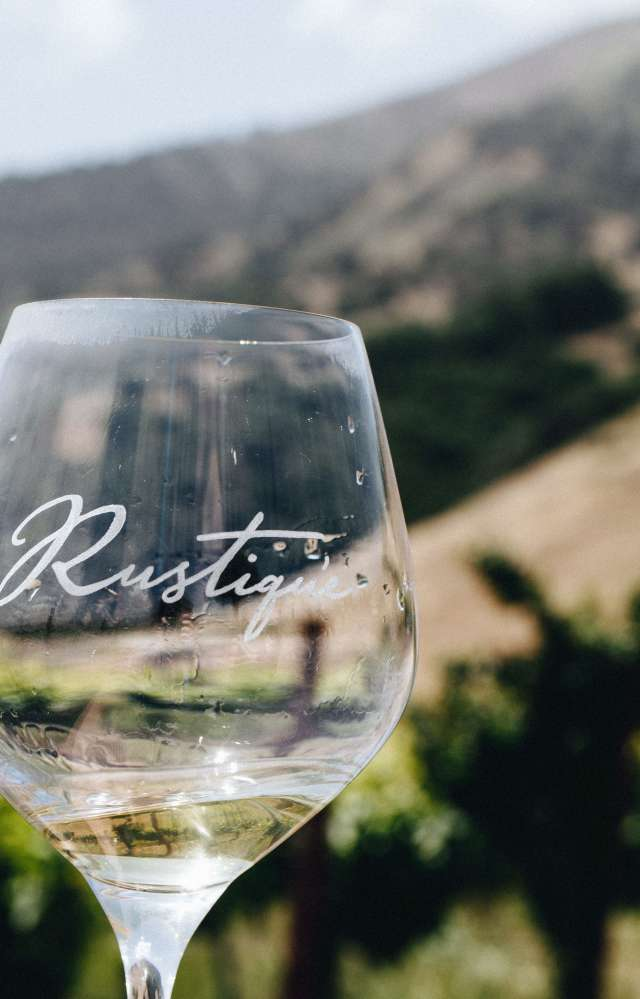 A glass of Rustique Wines in front of a scenic view of the Salinas Valley.
