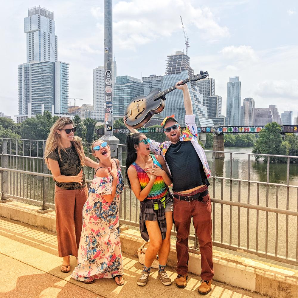 Four people posing on a bridge in front of Austin downtown skyline. Left to Right: woman grins at women beside her, woman places hand over heart and looks towards camera, woman places hands over her heart, man raises a guitar over his head
