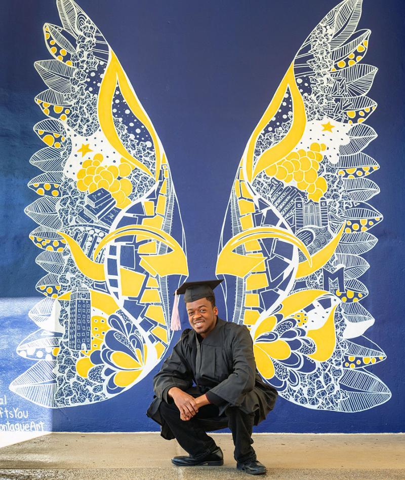 U-M Wings Mural with graduate posing