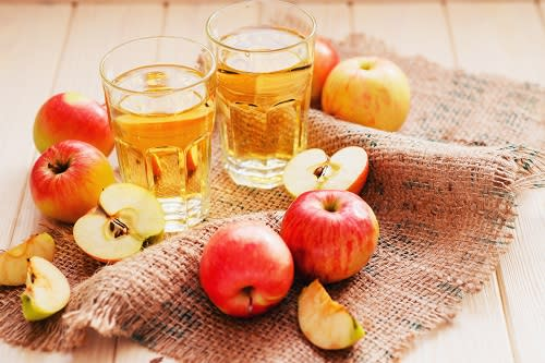 Two glasses of cider and a variety of apples - both whole and cut - sit on a burlap placemat on a wooden table