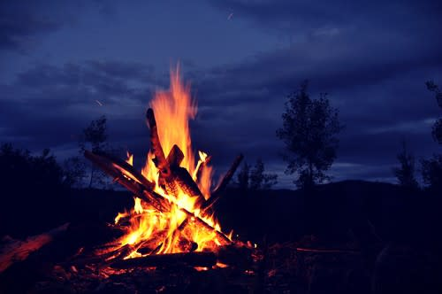 A large bonfire set against a midnight blue night sky with only black outlines of trees visible in the distance