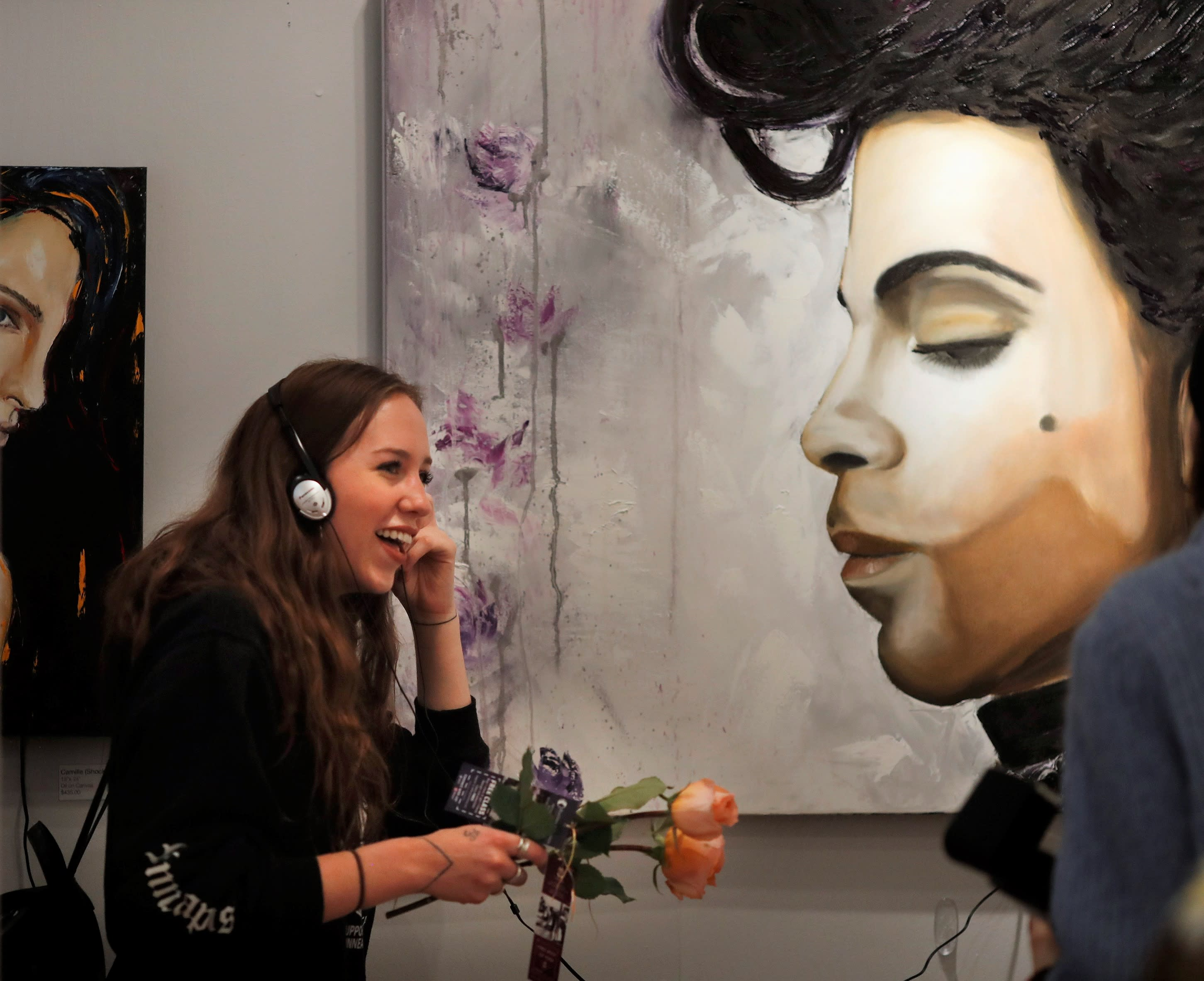 Women standing near large painting of Prince