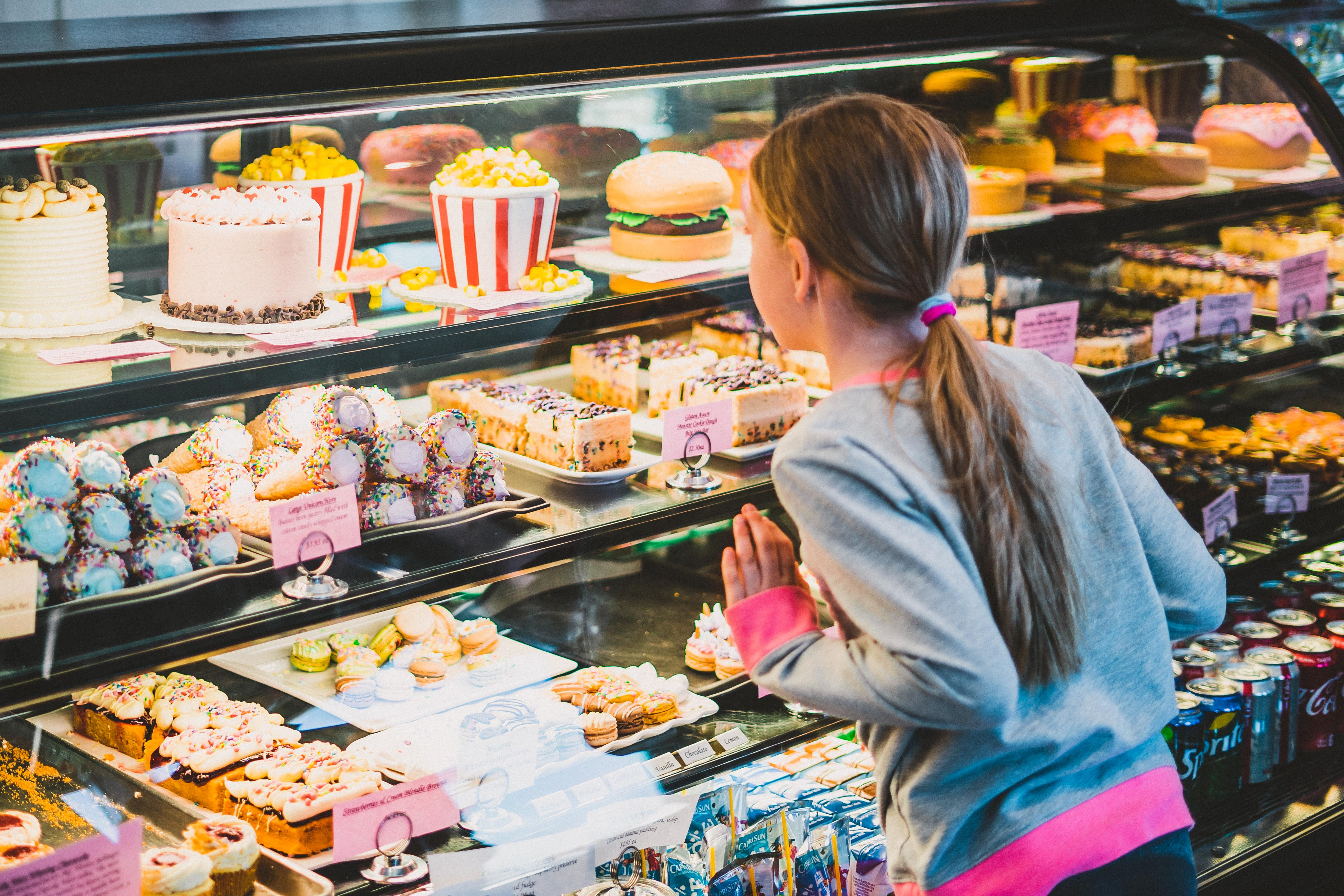 Little girl looking at desserts