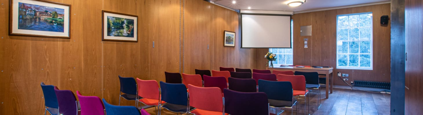 A wooden panelled room with large windows, chairs set theatre style and screen. A great meeting room in Cambridge.