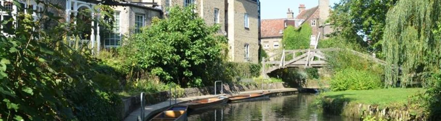 Darwin College with a wooden bridge crossing the River Cam. A great venue for hire in Cambridge.