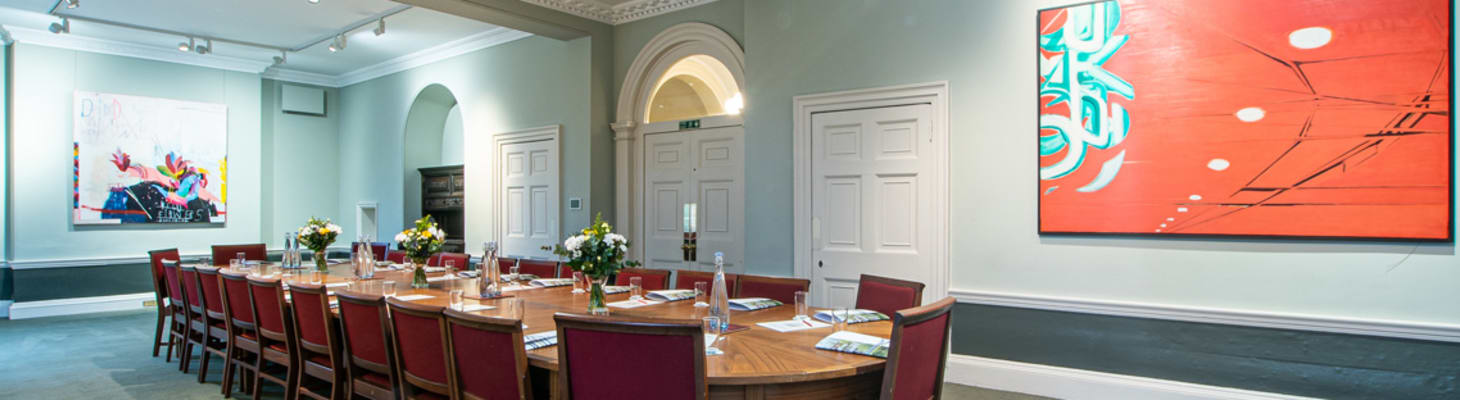 A large meeting room flooded with natural daylight. Set boardroom style, it is a perfect location for day meetings.