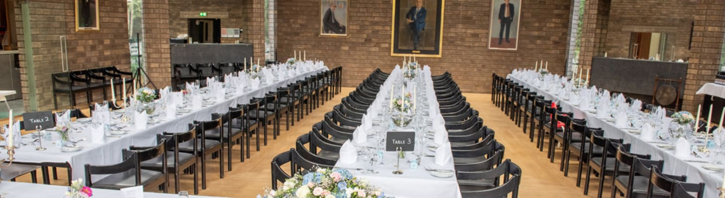 A traditional college dining hall set for a private dinner with white tablecloths and flowers.