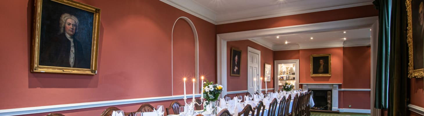 A beautiful, traditional room at Darwin College set for private dining with fresh flowers and candelabras.