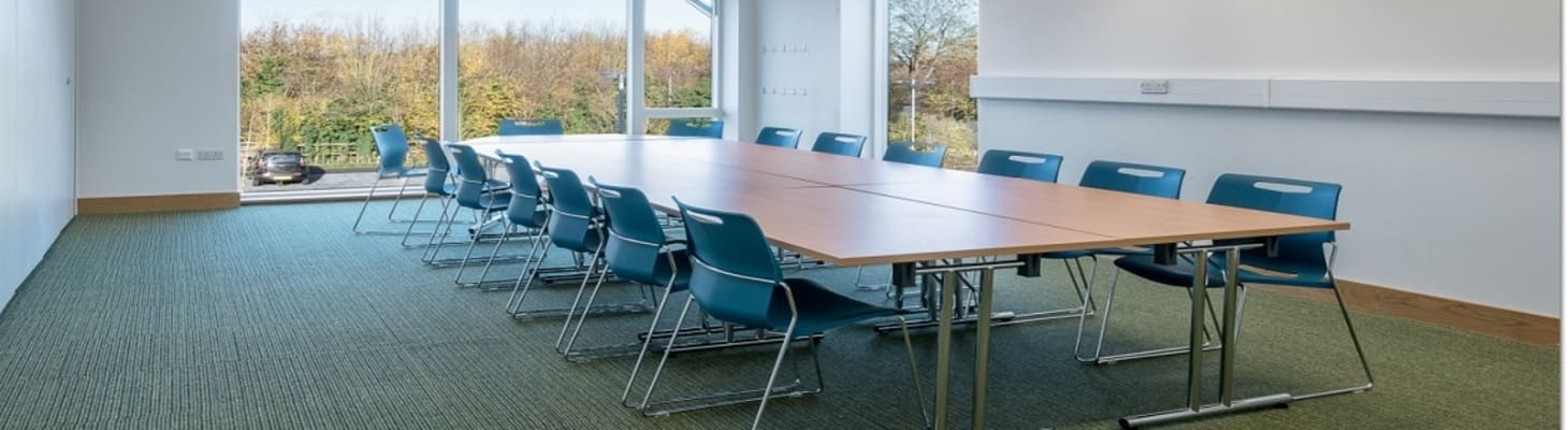 A bright room with large windows set boardroom style for a day meeting.