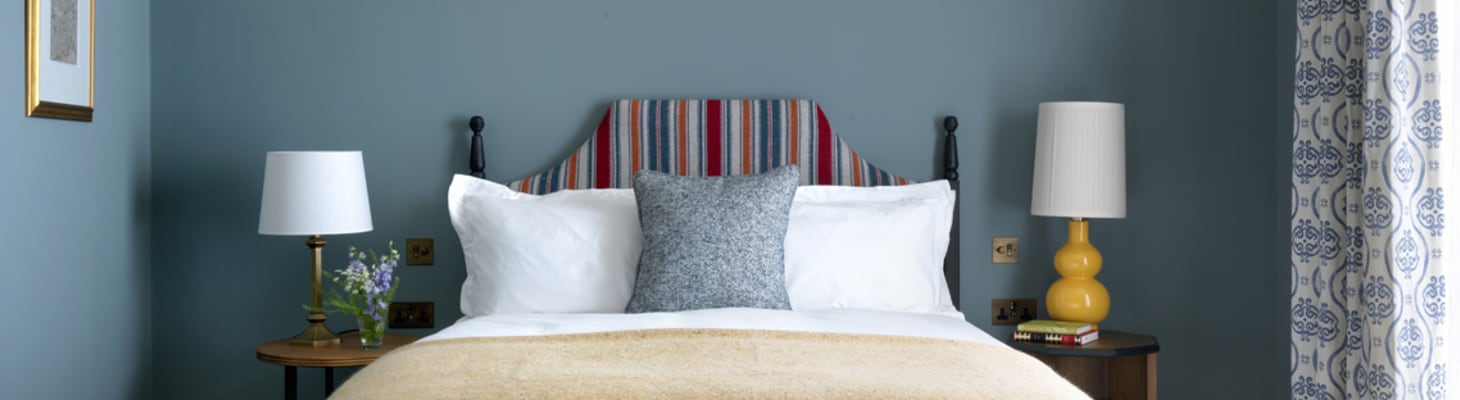 A bedroom at University Arms with double bed and plush cushions, perfect for delegates looking for conference accommodation.