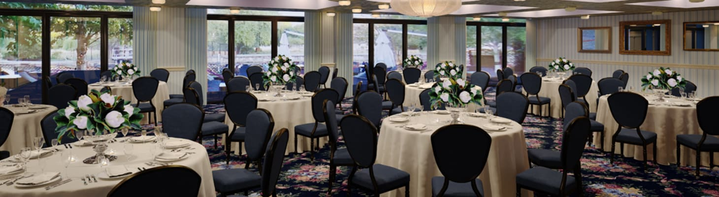 A large light and airy room with multiple floor to ceiling windows dressed for private dining on cabaret tables