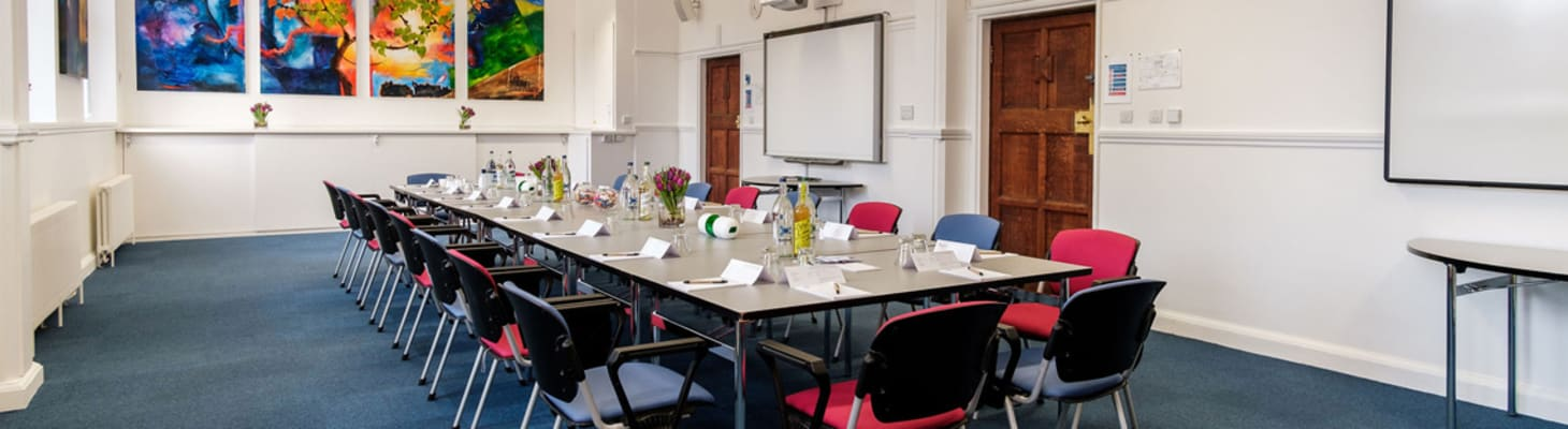 A spacious meeting room with colourful artwork. The room is set for a board meeting.
