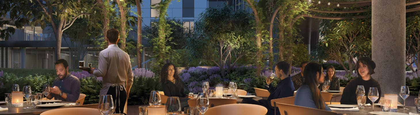 An outdoor dining space with round candlelit tables, fairy lights and greenery, perfect for private dining and events
