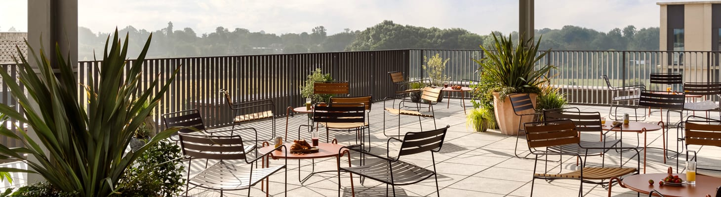 A bright and airy sociable roof top terrace with colourful tables and chairs; a unique space for gatherings, drinks receptions at the Turing Locke, Cambridge.