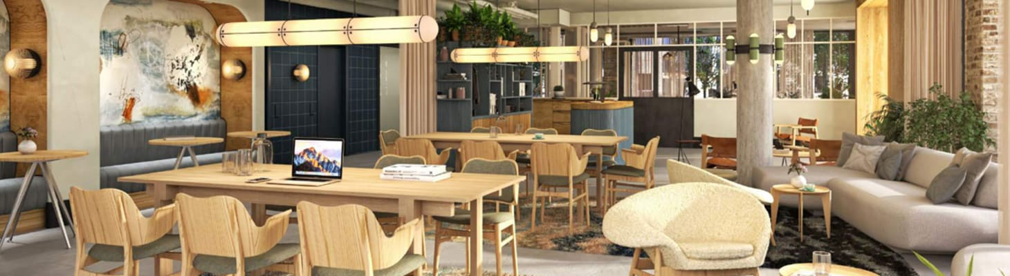 A large neutrally colored space for co working with wooden table and chairs, comfy soft furnishings perfect for room hire