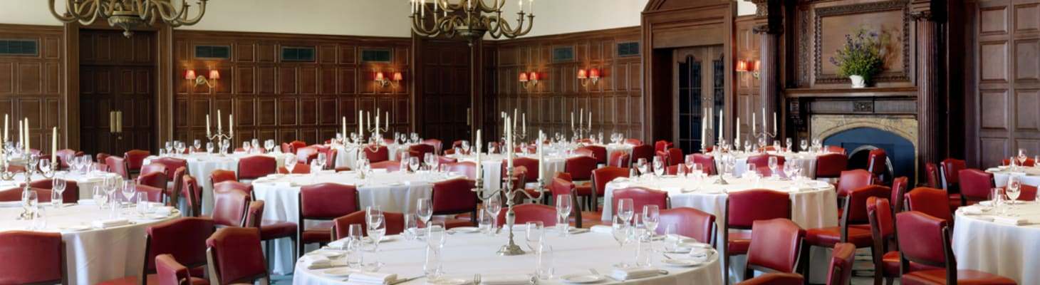 The exquisite ball room with grand chandeliers, set for dinner. An ideal gala dinner venue in Cambridge.