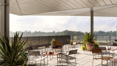 A bright and airy sociable roof top terrace with colourful tables and chairs making this a unique space for social gatherings and drinks receptions at Turing Locke, Cambridge.