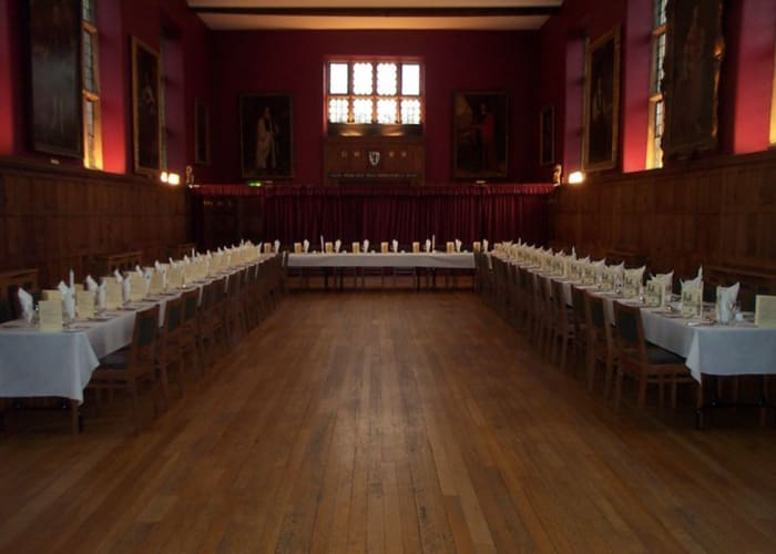 The Old Library, with long tables set for a private dinner, the wooden floor and panelled walls provide a classic Cambridge setting.