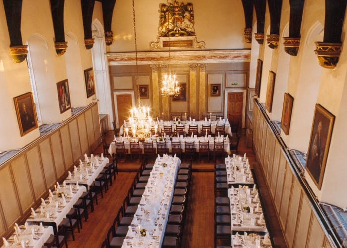 A magnificent room that has been the centre of College life since its founding in 1496, the Hall has a slightly raised dais to one end and a balcony at second floor level overlooking the room. On the walls are pictures of previous Masters and students of the college, as well as the Royal Arms of Queen Anne. Chandeliers suspended from the high vaulted ceilings provide adjustable levels of lighting to complement light from the tall windows.  Easily served by the kitchens below, the Hall provides a striking venue for fine dining or a formal dinner for up to 156 guests.