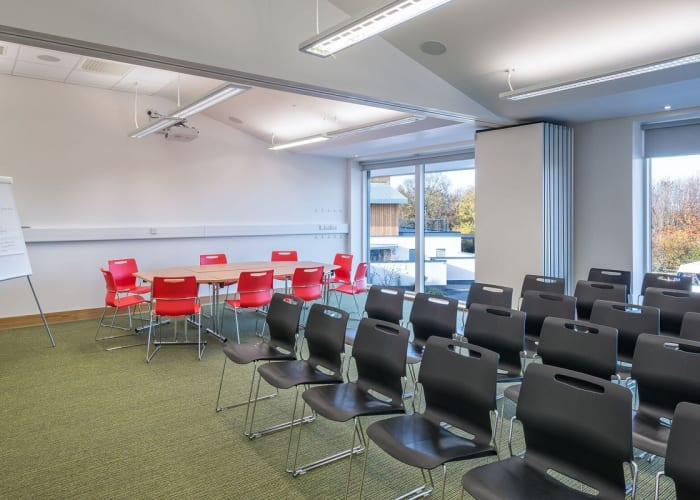 A meeting room with floor to ceiling windows, set theatre style one side and a table and chairs on the other side.