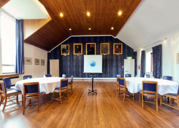 Set cabaret with a projector and screen, the Upper Hall is a bright room ideal for day meetings.