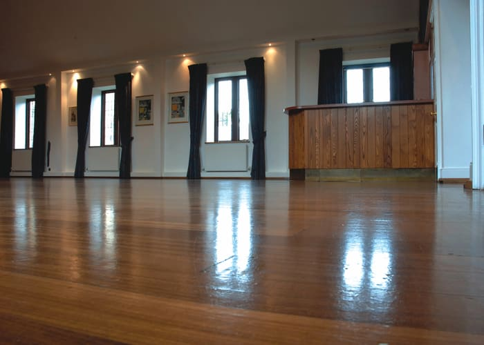 The Upper Hall, a flexible event space in Cambridge. Several windows flood the room with natural daylight which reflects of the wooden floor.