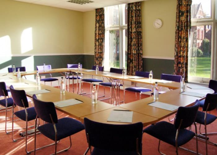 This comfortable conference room is appropriate for smaller group meetings. It provides a quiet and informal setting with plenty of natural daylight and stunning views of Woodlands Court.