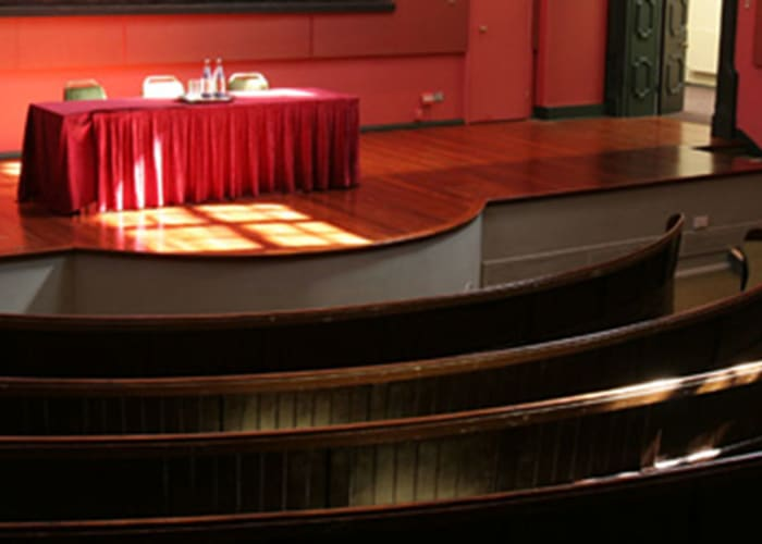 The striking Theatre building, situated in the heart of the College, was formerly the University Museum of Classical Archaeology. The Theatre retains much of its original character as a Victorian lecture room, with continuous upholstered bench seating in two tiers across a curving auditorium, a raised stage and gallery.  Fully refurbished in 2005, the Theatre is air-conditioned and has its own fully equipped projection room.