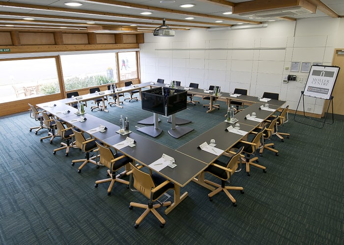Situated within the Study Centre, this room features views across Churchill College's grounds and has sliding external doors that open out onto a patio area.