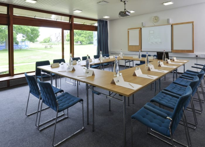 "Situated off the Wolfson Hall foyer, this room can be used in conjunction with the theatre as a breakout space or in its own right as a meeting room. The wall of windows with inspiring views across the grounds gives a sense of tranquillity, whilst plentiful daylight helps to illuminate the room which is equipped with an ""AV wall"" to facilitate seamless presentations as well as free WiFi access."