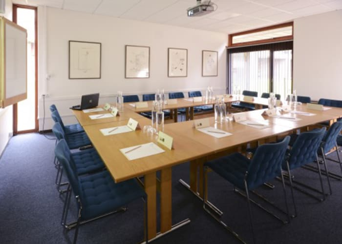 "A small training room featuring an ""AV wall"" and natural daylight. Conveniently located adjacent to the Wolfson Hall, it can be used for syndicate and break out meetings or as a Press or Green Room during larger events in the Wolfson Hall."