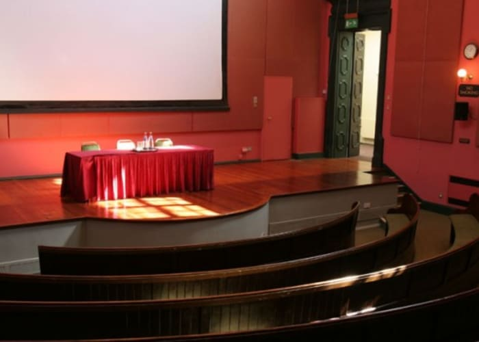 The striking Theatre building, situated in the heart of the College, was formerly the University Museum of Classical Archaeology. The Theatre retains much of its original character as a Victorian lecture room, with continuous upholstered bench seating in two tiers across a curving auditorium, a raised stage and gallery.  Fully refurbished in 2005, the Theatre is air-conditioned and has its own fully equipped projection room.  The adjacent Lubbock Room and foyer provides the ideal location for refreshments or break-out groups.  Capacity: Fixed Seating: 180