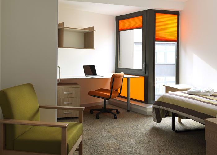A colourful and modern en suite room with single bed, desk, chair and lounge chair, great conference accommodation.