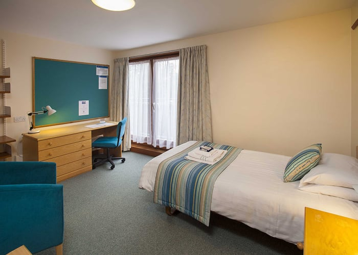Single rooms arranged in suites of two or three rooms which share a bathroom and toilet between them. These rooms are ideal for people travelling together and equally for the independent traveller who can still maintain their own privacy. Each of the rooms has its own locked door leading onto a corridor which is in turn secured from the staircase. All of these rooms are situated at the top of the building, accessible only by stairs. All have a balcony and many have a view over the beautiful gardens at Robinson College.