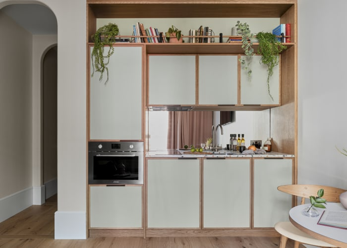 A sage green kitchenette complete with sink/ oven making this an accessible studio bedroom suite for conference accommodation