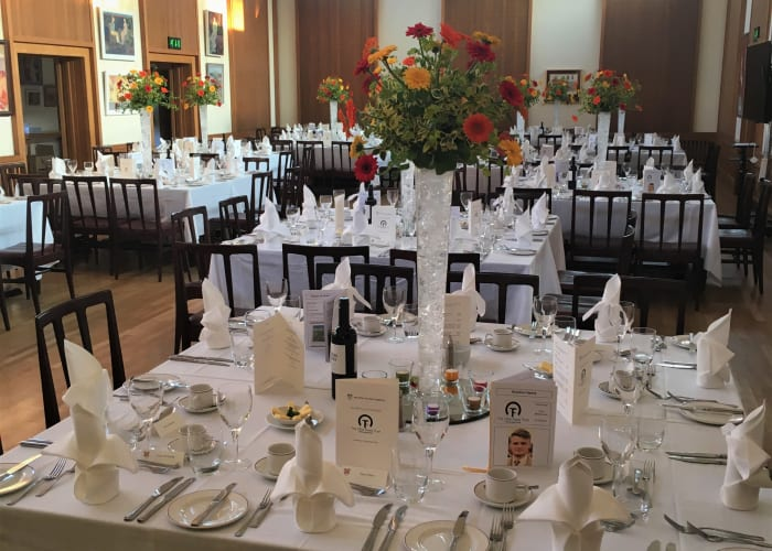 The dining hall set in cabaret layout for a gala dinner. Tall vases of fresh flowers make a statement on the tables.