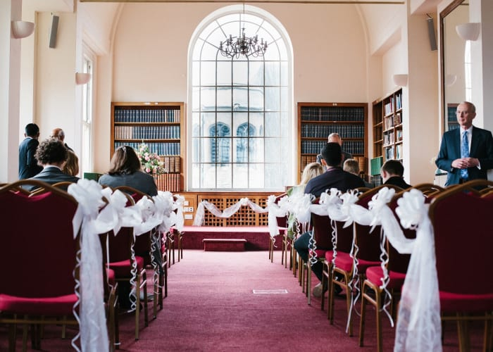 The Keynes Library, a traditional room, filled with wedding guests for a intimate civil ceremony.