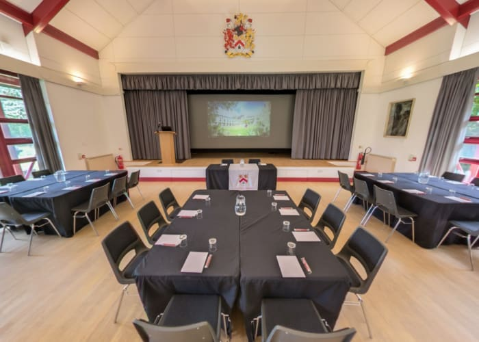 Set with three large tables in front of the stage, Lee Hall is a flexible event space in Cambridge.