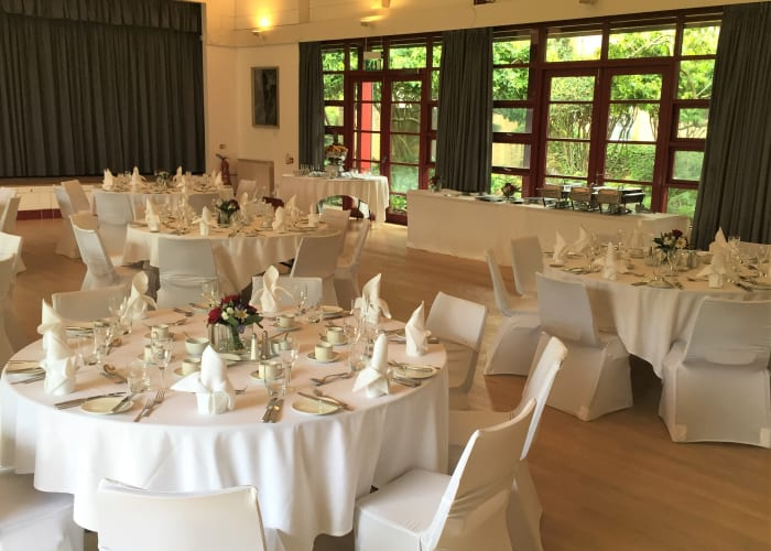 Lee Hall set for a gala dinner, round tables are decorated with white linen and pretty flowers.
