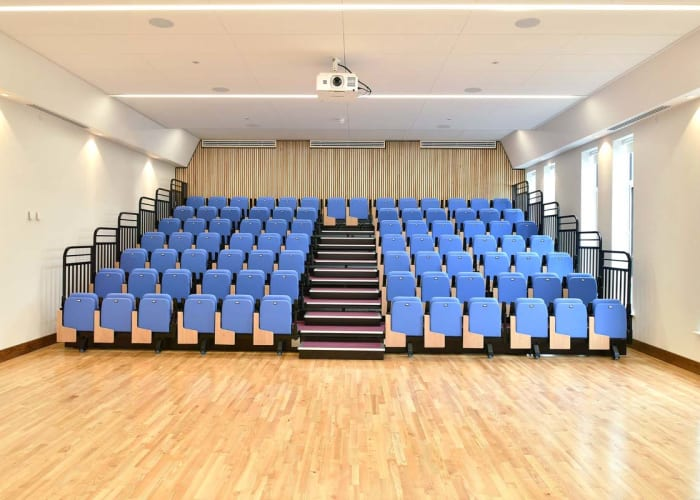 Modern bright spacious Auditorium with light wood flooring and white walls. There are rows of blue tiered chairs and a empty space at the front of the room
