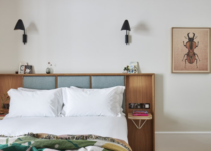 With a wooden panelled headboard, this cosy bedroom with white, fresh lined is perfect for conference accommodation.