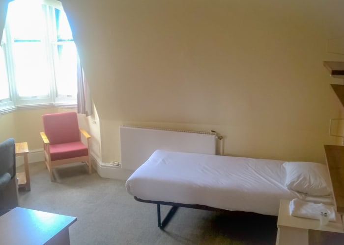 An Old Courts single traditional style bedroom with shared bathroom and kitchenette facilities.